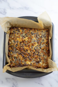 Keto Magic Bars in pan with parchment paper